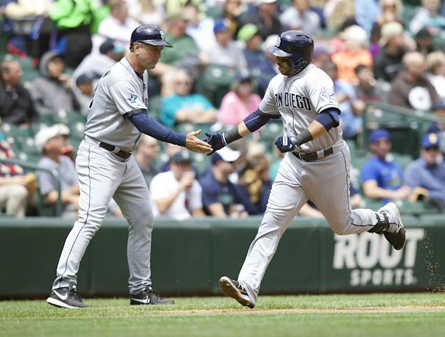 San Diego Padres' Rene Rivera is congratulated by third base coach Glenn Hoffman after Rivera hit a solo home run during the second inning a baseball game against the Seattle Mariners in Seattle, Tuesday, June 17, 2014. (AP Photo/Stephen Brashear)