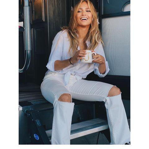 """<p>Days after Jennifer Lopez released a joint statement with Alex Rodriguez <a href=""""https://www.elle.com/uk/life-and-culture/a35838683/jennifer-lopez-alex-rodriguez-break-up-rumours/"""" rel=""""nofollow noopener"""" target=""""_blank"""" data-ylk=""""slk:announcing their split"""" class=""""link rapid-noclick-resp"""">announcing their split</a>, the mother-of-two posted a series of snaps on Instagram. The brunette can be seen sans engagement ring in all white while on set of her latest film Shotgun Wedding. She captioned the carousel of images of her wearing a tie-front white shirt and ripped white jeans: 'Coffee talk'.</p><p><a class=""""link rapid-noclick-resp"""" href=""""https://go.redirectingat.com?id=127X1599956&url=https%3A%2F%2Fwww.ssense.com%2Fen-gb%2Fwomen%2Fproduct%2Fagolde%2Fwhite-90s-mid-rise-loose-fit-jeans%2F6551341&sref=https%3A%2F%2Fwww.elle.com%2Fuk%2Ffashion%2Fcelebrity-style%2Fg28491328%2Fjennifer-lopez-best-looks%2F"""" rel=""""nofollow noopener"""" target=""""_blank"""" data-ylk=""""slk:SHOP RIPPED WHIE JEANS NOW"""">SHOP RIPPED WHIE JEANS NOW</a></p><p><a href=""""https://www.instagram.com/p/CN3AHrppZrK/"""" rel=""""nofollow noopener"""" target=""""_blank"""" data-ylk=""""slk:See the original post on Instagram"""" class=""""link rapid-noclick-resp"""">See the original post on Instagram</a></p>"""