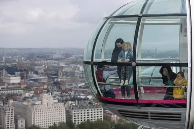 People ride in a capsule of the London Eye as the attraction reopens while COVID-19 restrictions continue to ease in London, U.K., on May 17, 2021.