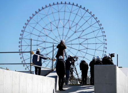 Media members report as a Ferris wheel is a background at the construction site of the Kasai Canoe Slalom Centre for Tokyo 2020 Olympic games in Tokyo, Japan February 12, 2019. REUTERS/Issei Kato