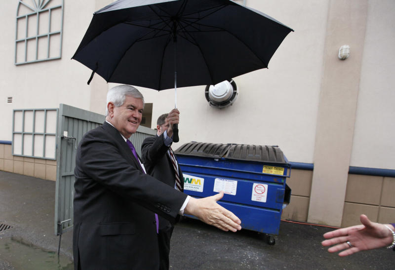 Republican presidential candidate, former House Speaker Newt Gingrich reaches out to greet a supporter as he comes in a back entrance at a campaign stop at a hotel Friday, Feb. 24, 2012, in Federal Way, Wash. (AP Photo/Elaine Thompson)