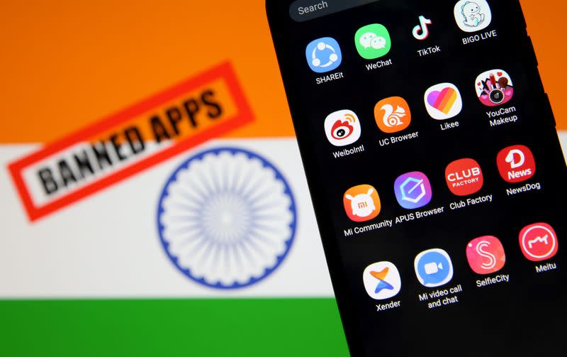 """FILE PHOTO: Smartphone with Chinese applications is seen in front of a displayed Indian flag and a """"Banned app"""" sign"""