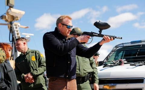 Acting Secretary of Defense Patrick Shanahan, center, fires a modified painted ball gun during a tour of the US-Mexico border