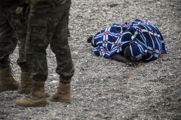A man lying on the ground after arriving in the Spanish territory at the border of Morocco and Spain, at the Spanish enclave of Ceuta, on Tuesday, May 18, 2021. Ceuta, a Spanish city of 85,000 in northern Africa, faces a humanitarian crisis after thousands of Moroccans took advantage of relaxed border control in their country to swim or paddle in inflatable boats into European soil. Around 6,000 people had crossed by Tuesday morning since the first arrivals began in the early hours of Monday, including 1,500 who are presumed to be teenagers. (AP Photo/Javier Fergo)