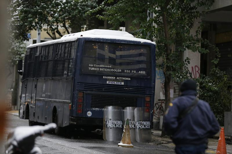 A policeman walks outside the Pan-Hellenic Socialist Movement (PASOK) offices after a gunman opened fire at the bus, left, in Athens, on Tuesday, Jan. 10, 2017. Authorities say a police officer has been wounded after shots were fired outside the offices of the political party in an area of Athens where anarchist groups frequently clash with police and attack symbols of authority. (AP Photo/Thanassis Stavrakis)