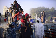 Rohingya refugees board a naval ship to be transported to an isolated island in the Bay of Bengal, in Chittagong, Bangladesh, Tuesday, Dec. 29, 2020. Officials in Bangladesh sent a second group of Rohingya refugees to the island on Monday despite calls by human rights groups for a halt to the process. The Prime Minister's Office said in a statement that more than 1,500 Rohingya refugees left Cox's Bazar voluntarily under government management. Authorities say the refugees were selected for relocation based on their willingness, and that no pressure was applied on them. But several human rights and activist groups say some refugees have been forced to go to the island, located 21 miles (34 kilometers) from the mainland. (AP Photo/Mahmud Hossain Opu)