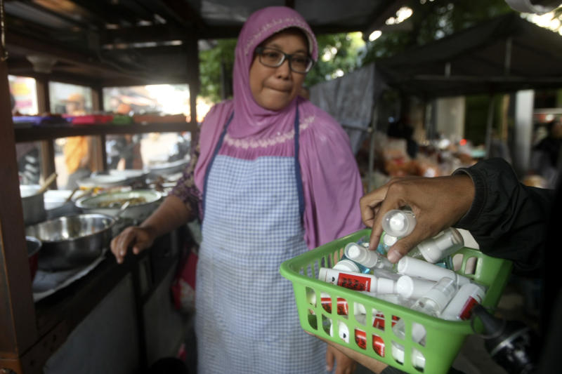 In this Thursday, March 26, 2020 photo, an activist distribute hand sanitizers and soaps to a street food vendor in Yogyakarta, Indonesia. A group of students from several universities in the central Java city has distributed soaps and hand sanitizers to informal daily workers whose incomes are affected by the coronavirus outbreak. (AP Photo/Fahmi Rosyidi)