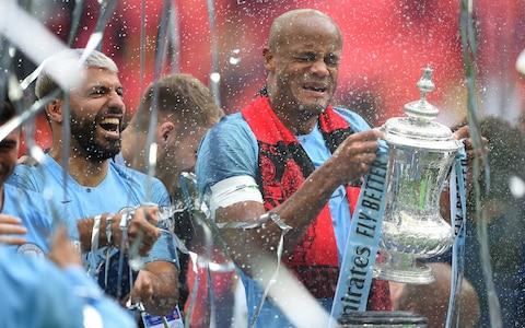 Vincent Kompany of Manchester City is sprayed with champagne as he celebrates with the FA Cup trophy following his team's victory in the FA Cup Final match between Manchester City and Watford - Credit: Getty images