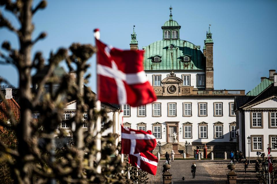 Danish flags flutter in front of Fredensborg Palace in Fredensborg, Denmark