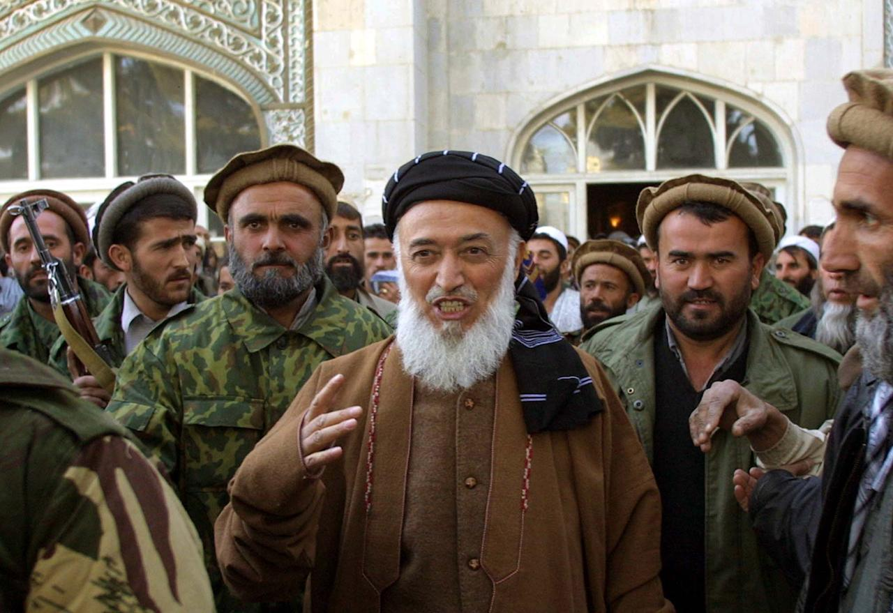 FILE - This Friday, Nov. 23, 2001 file photo shows former Afghan President Burhanuddin Rabbani as he emerges from the Pul-e-Khishti mosque after Friday prayers, surrounded by United Front bodyguards and supporters, in the capital Kabul, Afghanistan. A Kabul police official said Tuesday Sept. 20, 2011 that former Afghan President Burhanuddin Rabbani was killed by a suicide bomber who had explosives in his turban. A presidential spokesman says Afghan President Hamid Karzai is cutting short his trip to the United Nations in New York to return to Kabul. (AP Photo/Brennan Linsley)