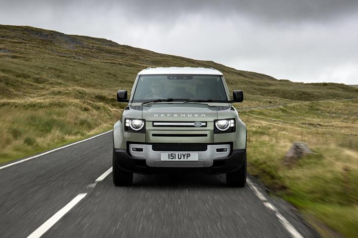 A Land Rover Defender driving down a country road