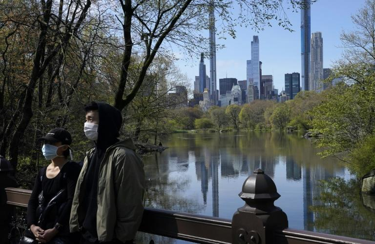 The Midtown Manhattan skyline is reflected in the water as people in masks walk along the lake in Central Park (AFP Photo/TIMOTHY A. CLARY)