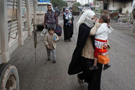 Displaced Iraqi people from the Bab al-Tob area in Mosul flee their homes after clashes to reach safe areas as Iraqi forces battle with Islamic State militants in the city of Mosul