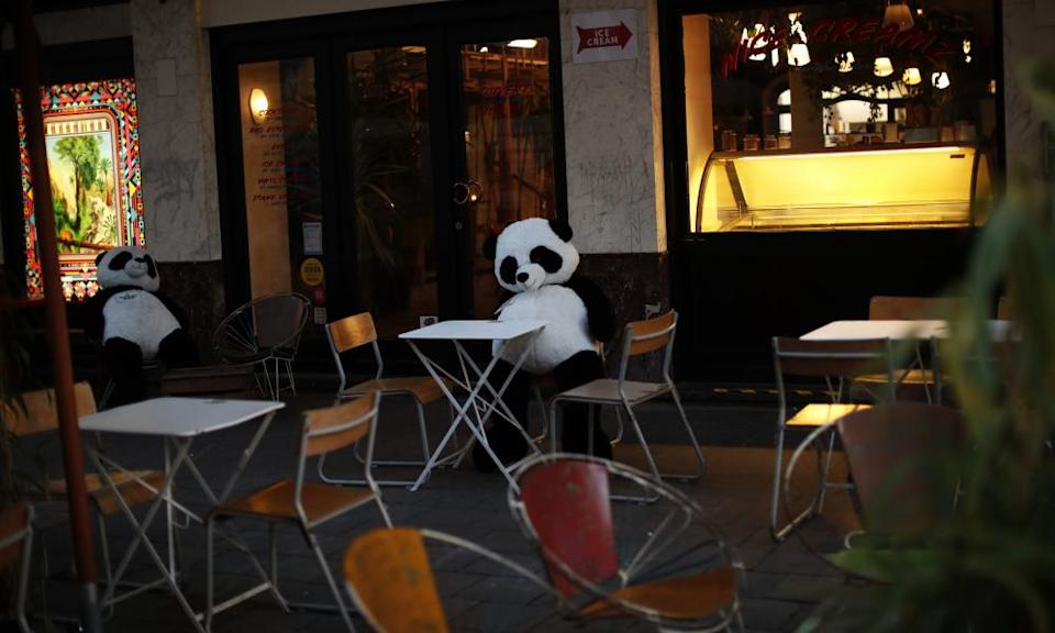 Soft toys sit on an empty terrace of a restaurant in downtown Brussels