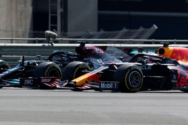 Lewis Hamilton (left) and Max Verstappen take a curve side by side at the start of the race