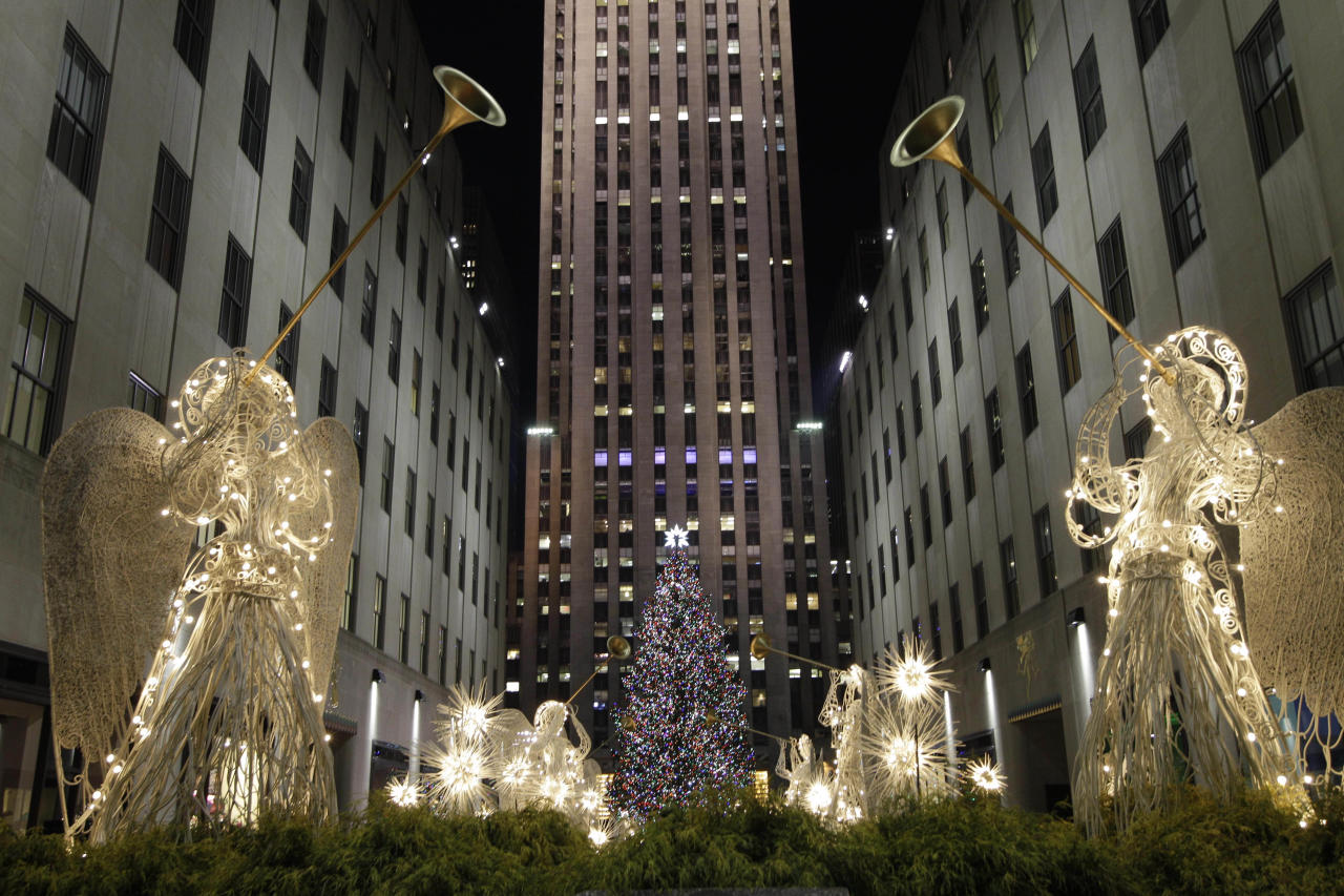 Angels decorations frame the Rockefeller Center Christmas tree after it was lit during the 80th annual tree lighting ceremony at Rockefeller Center in New York, Wednesday, Nov. 28, 2012. (AP Photo/Kathy Willens)