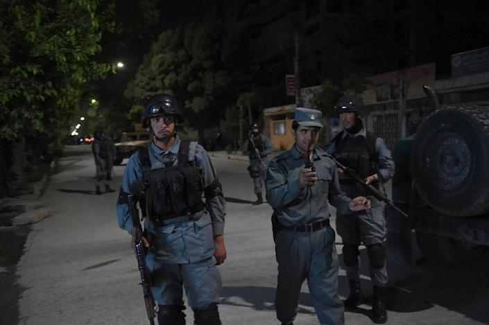 Afghan policemen stand guard near the Park Place guesthouse in Kabul on May 13, 2015 after gunmen stormed the guesthouse ahead of a planned concert (AFP Photo/Shah Marai)