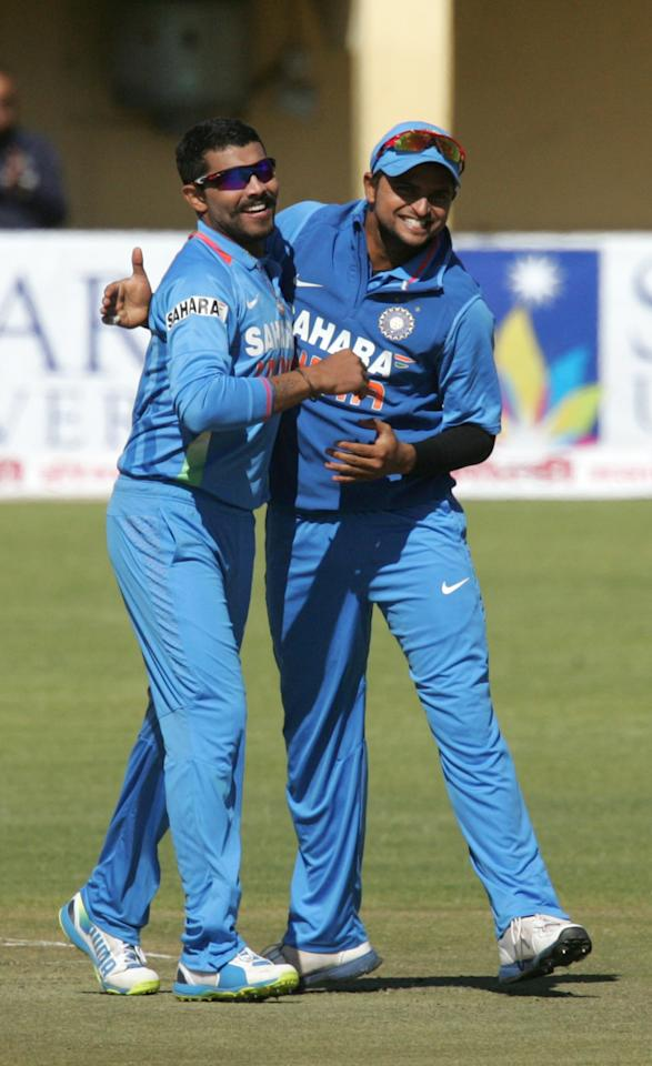 India players Ravindra Jadeja (L) and Suresh Raina celebrate a wicket during the 4th match of the 5-match cricket ODI series between Zimbabwe and India at Queen's Sports Club in Harare on August 1, 2013. AFP PHOTO / Jekesai Njikizana        (Photo credit should read JEKESAI NJIKIZANA/AFP/Getty Images)