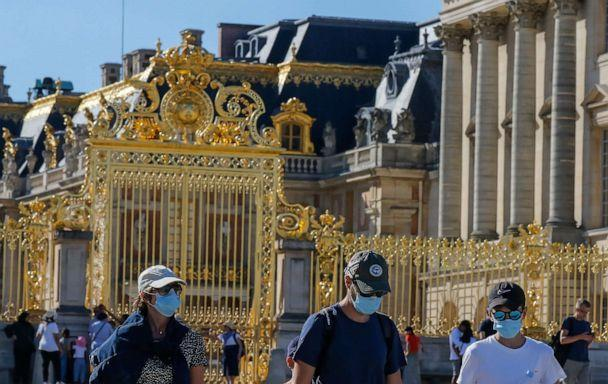 PHOTO: People wearing face masks to prevent against the spread of COVID-19 walk past the Gate of Honor at the Palace of Versailles near Paris, France, on Aug. 4, 2020. (Michel Euler/AP)