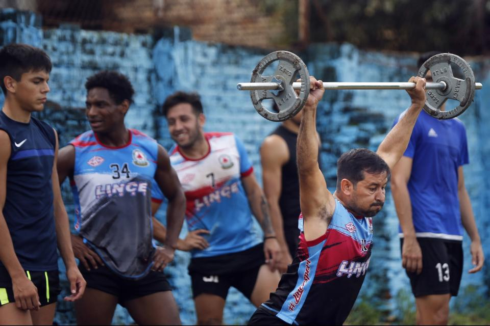 Striker Nicolas Caballero of the second division Resistencia football club, lifts weights during a training session in Asuncion, Paraguay, Tuesday, Feb. 2, 2021. Caballero, 32, who hasn't been paid by his club for more than a year, now has a food stall that sells barbecue on the streets to survive during the COVID-19 pandemic. (AP Photo/Jorge Saenz)