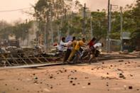 People run past makeshift barricades set up by anti-coup demonstrators in Yangon's Hlaing Tharyar township