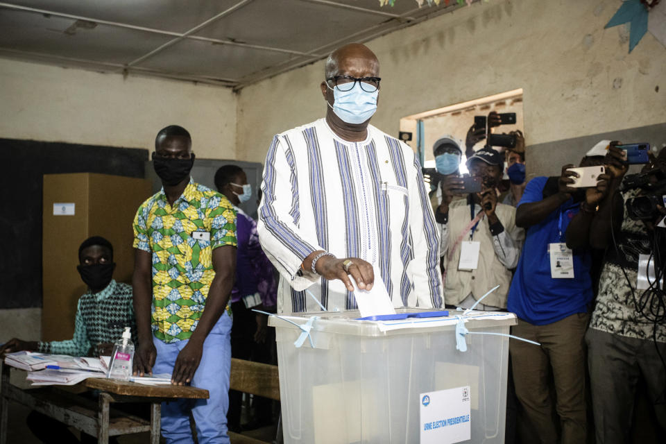 Burkina Faso President Roch Kabore casts his ballot in the presidential and legislative elections in Ouagadougou Sunday Nov. 22, 2020. Voters went to the polls in Burkina Faso on Sunday for the elections that have been marred by ongoing extremist violence in this landlocked West African nation. (AP Photo/Sophie Garcia)