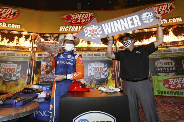 In this photo provided by Chris Owens/INDYCAR Series, Scott Dixon, left, holds the winner's trophy in Victory Lane as Texas Motor Speedway President Eddie Gossage, right, practices social distancing after an IndyCar auto race in Fort Worth, Texas, Saturday, June 6, 2020. (Chris Owens/INDYCAR Series via AP)