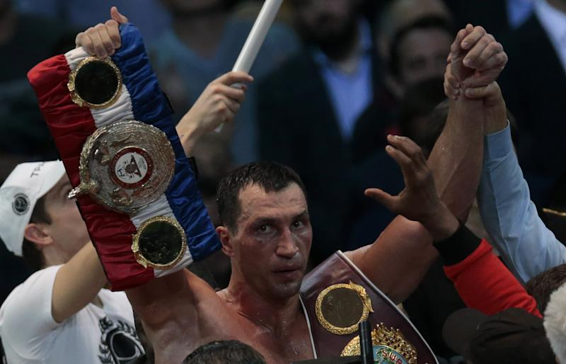 Heavyweight champion Wladimir Klitschko, of Ukraine, holds two of his belts after a bout with Alexander Povetkin, of Russia, unseen, at the Olympic Stadium, in Moscow, Russia, on Saturday, Oct. 5, 2013. Wladimir Klitschko successfully defended his WBA and IBF titles. (AP Photo/Ivan Sekretarev)