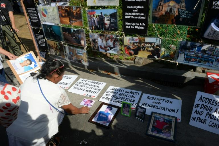 A relative of a victim of extra-judicial killings in President Rodrigo Duterte's drug war arranges photographs of victims on the grounds of a church in Manila on March 1, 2017