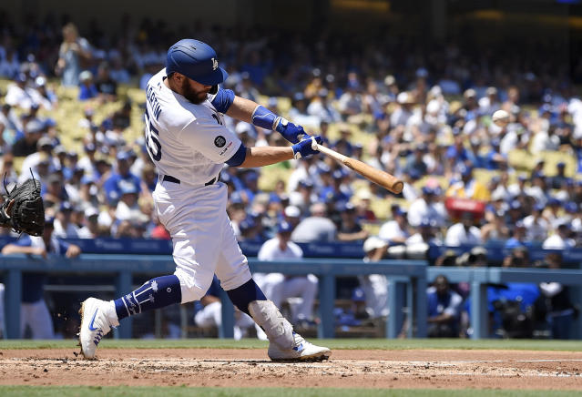 Los Angeles Dodgers' Russell Martin, left, hits a two-run home run during the second inning of a baseball game against the San Diego Padres Sunday, Aug. 4, 2019, in Los Angeles. (AP Photo/Mark J. Terrill)