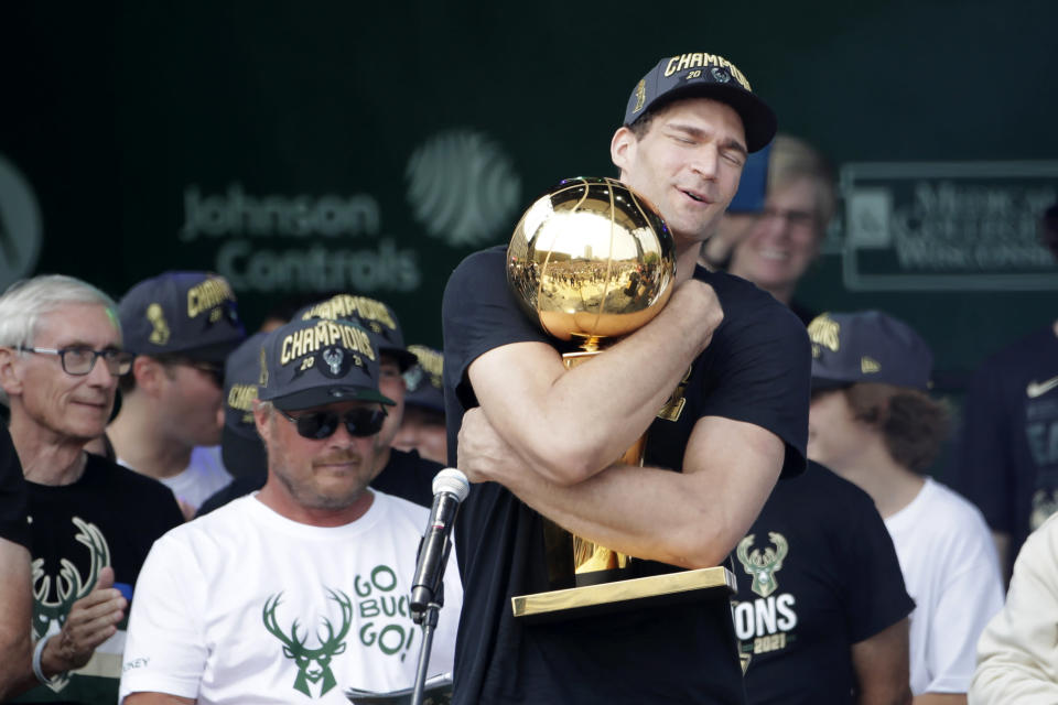 Milwaukee Bucks' Brook Lopez hugs the NBA Championship trophy during a parade celebrating the Milwaukee Bucks' NBA Championship basketball team Thursday, July 22, 2021, in Milwaukee. (AP Photo/Aaron Gash)