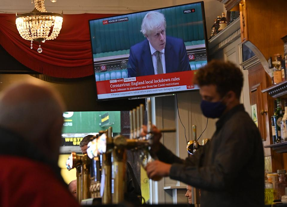 A television shows Britain's Prime Minister Boris Johnson speaking in the House of Commons in London, as customers sit atthe bar inside the Richmond Pub in Liverpool, north west England on October 12, 2020, as new local lockdown measures are set to be imposed to help stem a second wave of the novel coronavirus COVID-19. - British Prime Minister Boris Johnson presented a new three-tiered alert system for coronavirus cases in England on Monday, with Liverpool in the northwest expected to be the only city placed in the top category. Like governments throughout Europe, Johnson's conservative cabinet is seeking to balance bringing down the rate of new infections against concern about the economy and frustration among voters. (Photo by Paul ELLIS / AFP) (Photo by PAUL ELLIS/AFP via Getty Images)