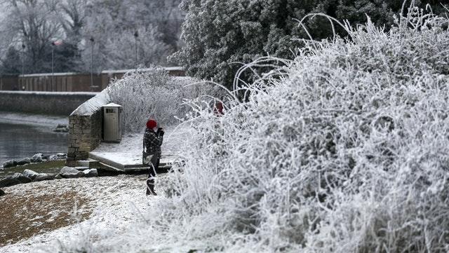 A walker photographs the snow and frost in Marchwood near Southampton
