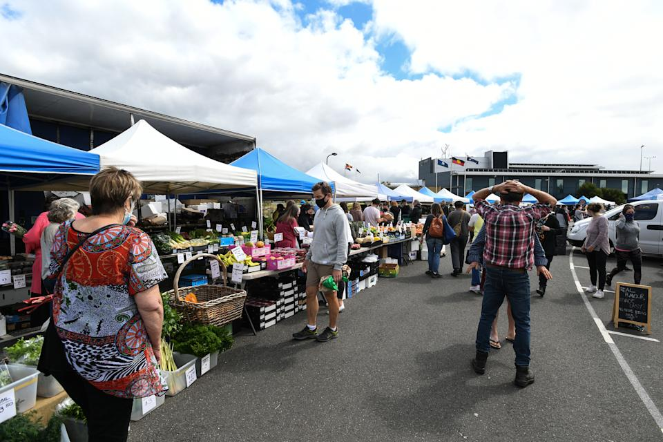 People are seen at a farmer's market in Torquay, Victoria.