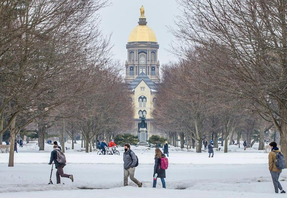 Students cross Notre Dame's campus between classes on Monday, Feb. 22, 2021, in South Bend.