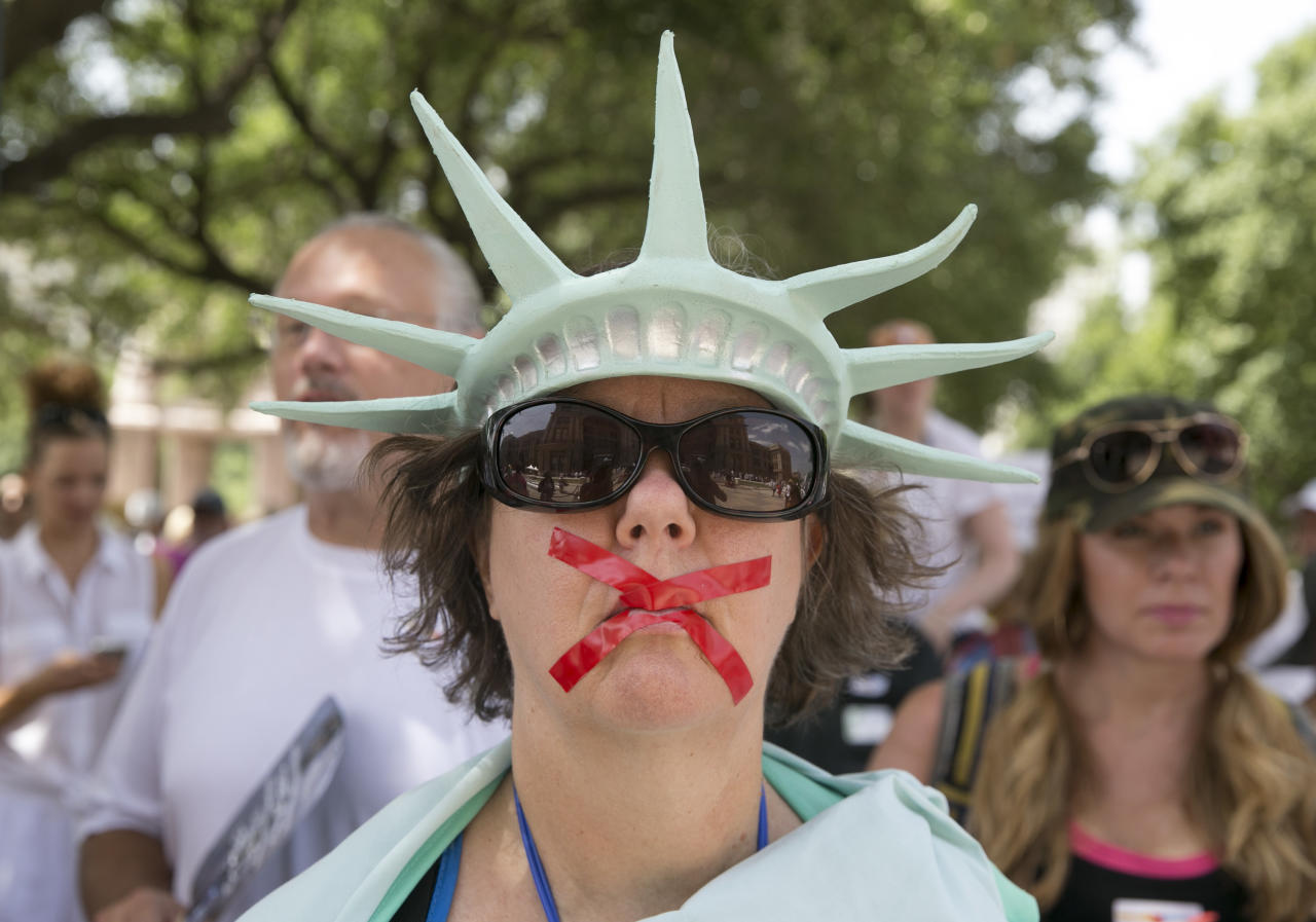 <p>Deborah Campbell, dressed as the Statue of Liberty with red tape over her mouth, attends the Families Belong Together rally at the Capitol in Austin, Texas, on Saturday, June 30, 2018. (Photo: Jay Janner/Austin American-Statesman via AP) </p>