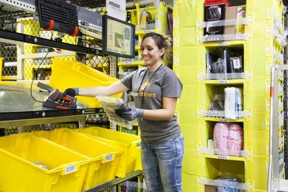 An Amazon fulfillment center employee picking items from bins preparing them for shipment.