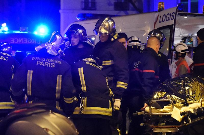 Firefighters and rescuers evacuate injured people near the Bataclan concert hall in central Paris, on November 14, 2015