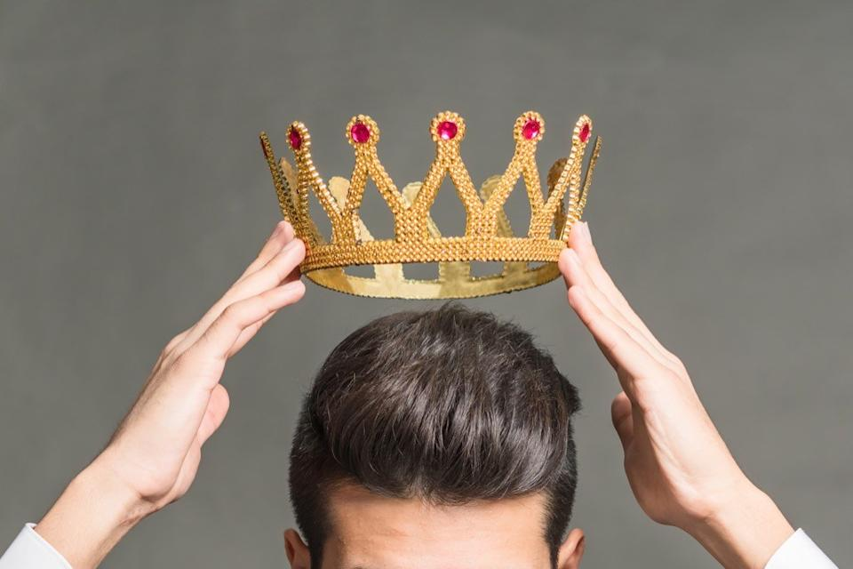 Man holding a crown above his head.
