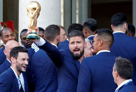 France player Olivier Giroud holds the trophy with team mates before a reception to honour the France soccer team after their victory in the 2018 Russia Soccer World Cup, at the Elysee Palace in Paris, France, July 16, 2018. REUTERS/Philippe Wojazer