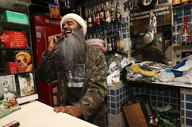 SAO PAULO, BRAZIL - APRIL 29: Osama bin Laden lookalike Ceara Francisco Helder Braga Fernandes laughs while chatting on the phone in his 'Bar do Bin Laden' on April 29, 2014 in Sao Paulo, Brazil. Braga says he was known as the 'Beard Man' before 9/11 but became known as a Bin Laden lookalike following the 9/11 attacks. He says he is Christian and continues to play the role to support his business. (Photo by Mario Tama/Getty Images)