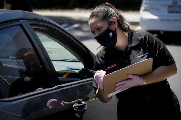 PHOTO: Jennifer Majano helps an job seeker fill out an application at a drive up job fair for Allied Universal, May 6, 2020, in Gardena, Calif. (Chris Carlson/AP)