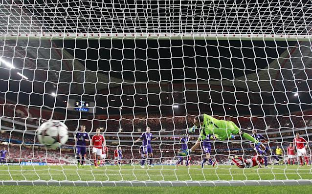 Anderlecht's goalkeeper Silvio Proto dives as the shot by Benfica's Benfica's Luisao, bottom right enters the net during the Champions League group C soccer match between Benfica and Anderlecht Tuesday, Sept. 17, 2013, at Benfica's Luz stadium in Lisbon. (AP Photo/Armando Franca)