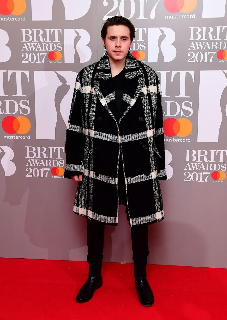 <p>The Beckham offspring was suave in a checked coat. <i>[Photo: PA]</i> </p>
