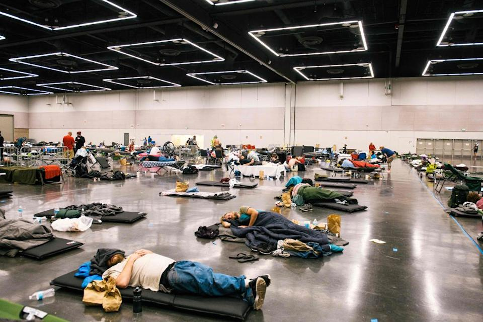 People lying on mats inside the Oregon Convention Center cooling station as the state struggles to cope with soaring temperatures.