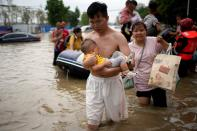 FILE PHOTO: Man holding a baby wades through a flooded road following heavy rainfall in Zhengzhou