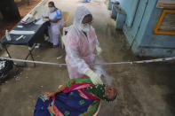 A health worker collects a nasal swab sample to test for COVID-19 in Hyderabad, India, Monday, Sept. 21, 2020. The nation of 1.3 billion people is expected to become the coronavirus pandemic's worst-hit country within weeks, surpassing the United States.(AP Photo/Mahesh Kumar A.)