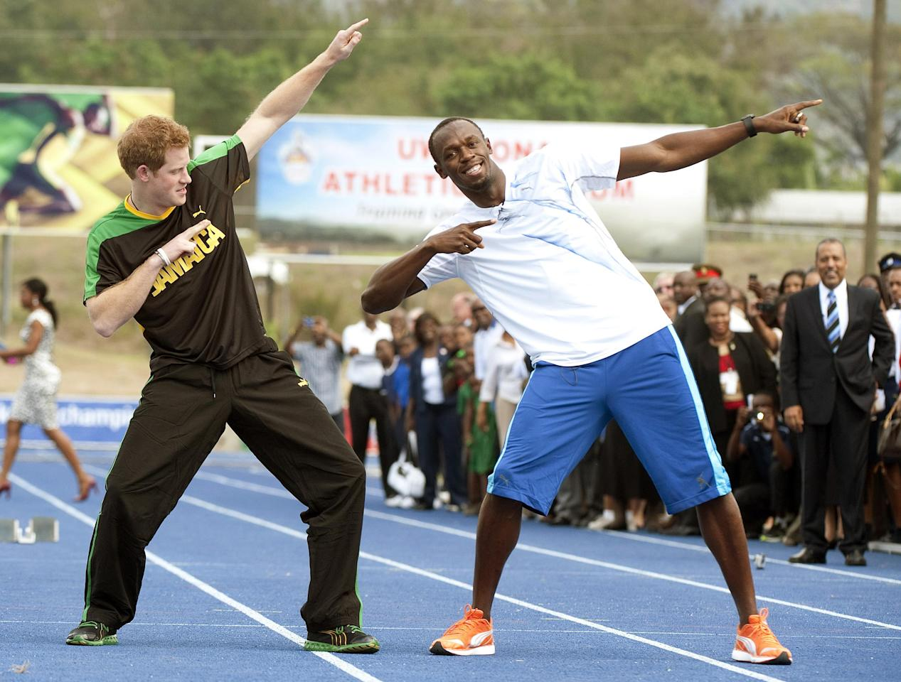 Britain's Prince Harry follows the signature victory gesture of Olympic sprint champion Usain Bolt, Tuesday March 6 2012 following a mock race at the University of the West Indies, in Jamaica. Harry is touring the Caribbean as part of a Diamond Jubilee tour in honor of Queen Elizabeth II as she celebrates 60 years on the throne. His visit comes as the new prime minister, Portia Simpson Miller, has called anew for the severing of ties with the British monarchy. (AP PhotoJohn Stillwell/PA) UNITED KINGDOM OUT NO SALES NO ARCHIVE