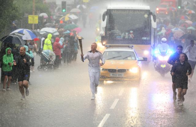 This photo made available by LOCOG shows Glenn Chambers carrying the Olympic Flame on the Torch Relay leg between Edwinstowe and Mansfield, near Lincoln, eastern England, during a heavy downpour, on Day 41 of the London 2012 Olympic Torch Relay, Thursday June 28, 2012. (AP Photo/LOCOG, Chris Radburn)