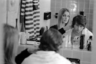 <p>Actress Sharon Tate trims a few inches off of the back of her husband's, director Roman Polanski, hair in the master bathroom of their London apartment. </p>